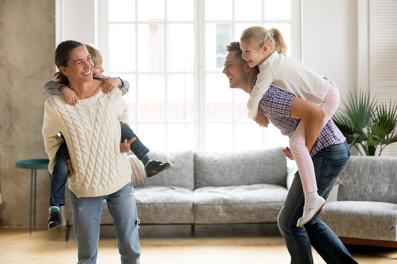 Laughing Parents Holding Kids On Back Giving Children Piggyback Ride Playing Together At Home, Cheerful Family Enjoying Active Funny Game Together, Siblings Having Fun With Mom And Dad On Weekend